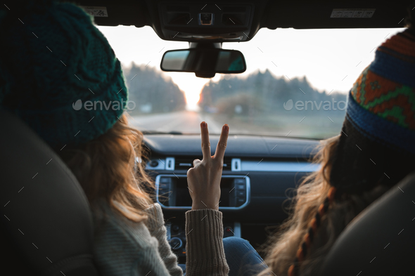 two girls sitting in the car, looking forward, showing peace sign - Stock Photo - Images