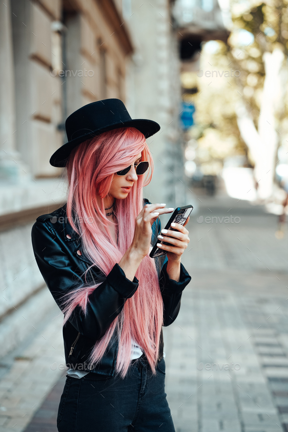girl with pink hair with a smartphone - Stock Photo - Images