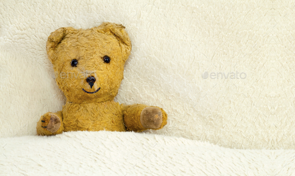 Cute toy bear lying in the bed - Stock Photo - Images
