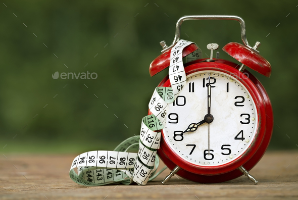 Retro alarm clock and a tape measure - Stock Photo - Images