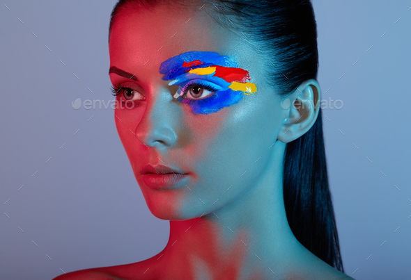 Fashion model woman with colored face painted - Stock Photo - Images
