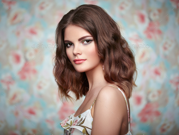 Portrait of young beautiful woman on a background of flowers - Stock Photo - Images