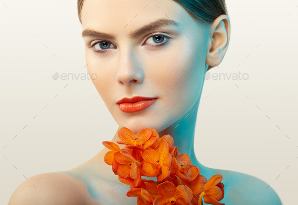 Portrait of beautiful young woman with orchid - Stock Photo - Images