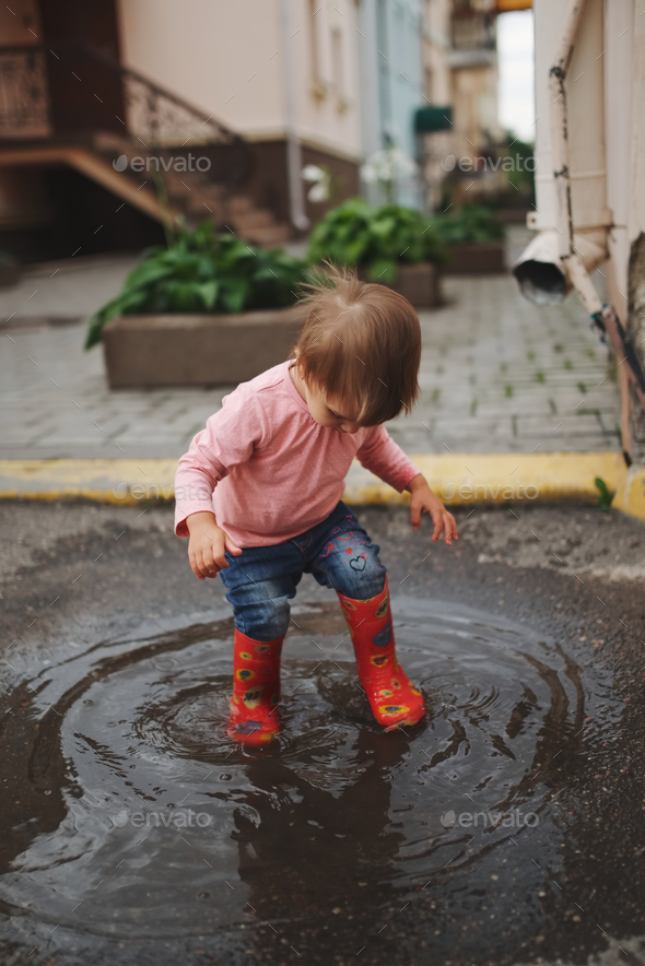 girl plays in the puddle outdoors - Stock Photo - Images
