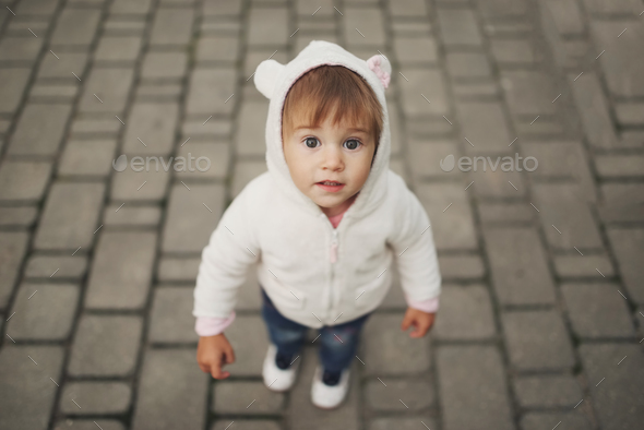 cute little girl in hood with ears - Stock Photo - Images