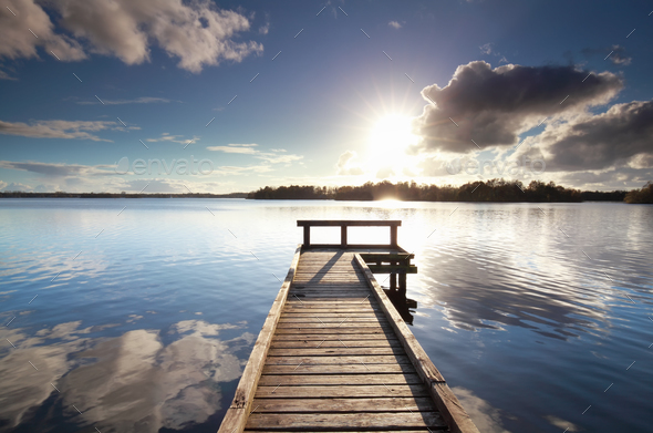 sunshine over wooden pier on big lake - Stock Photo - Images