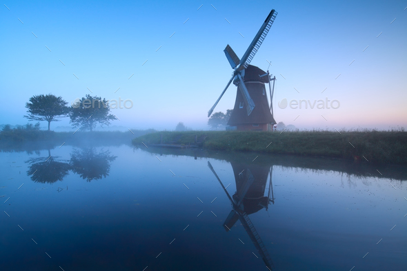 Dutch windmill by lake in dusk - Stock Photo - Images