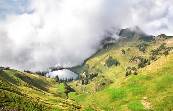dense fog starts to cover alpine lake - Stock Photo - Images