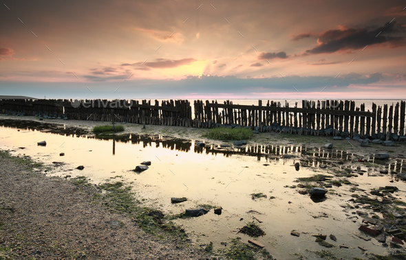 old breakwater on coast at sunset - Stock Photo - Images