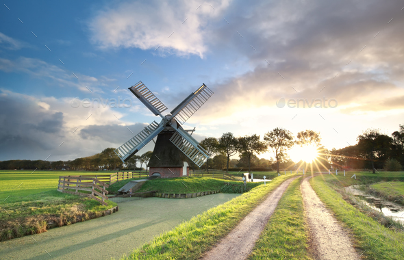 windmill, rural road and river at sunrise - Stock Photo - Images