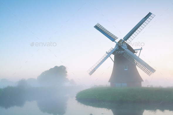 charming windmill in morning fog - Stock Photo - Images