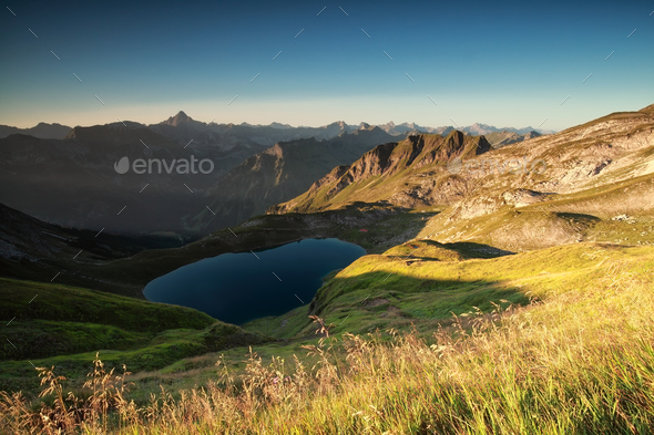 sunrise over alpine peaks and lake - Stock Photo - Images