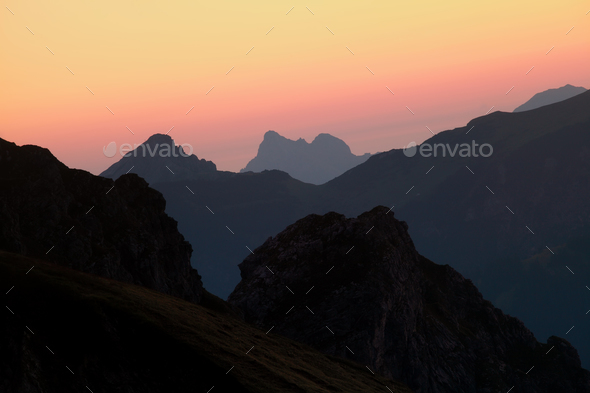 mountain silhouettes over sky at sunrise - Stock Photo - Images