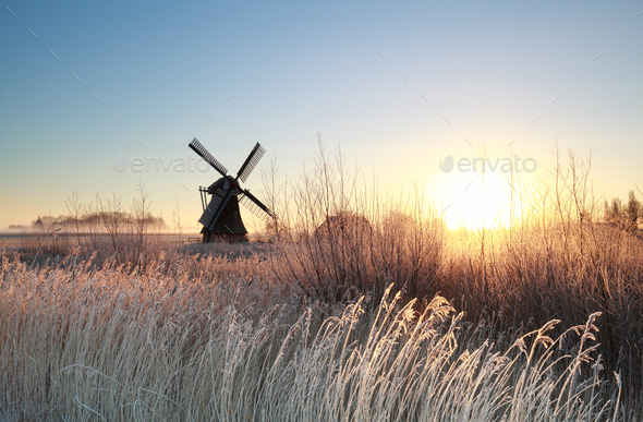 sunrise over Dutch windmill on frosty morning - Stock Photo - Images