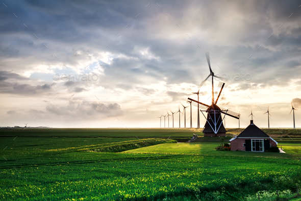 sunshine behind old windmill and modern mills - Stock Photo - Images