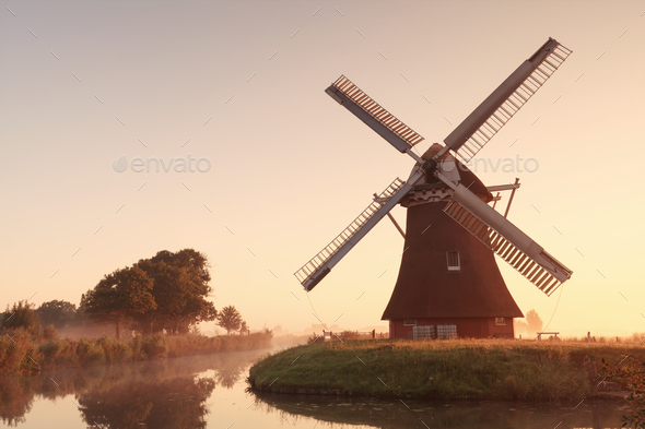 charming windmill by river at sunrise - Stock Photo - Images