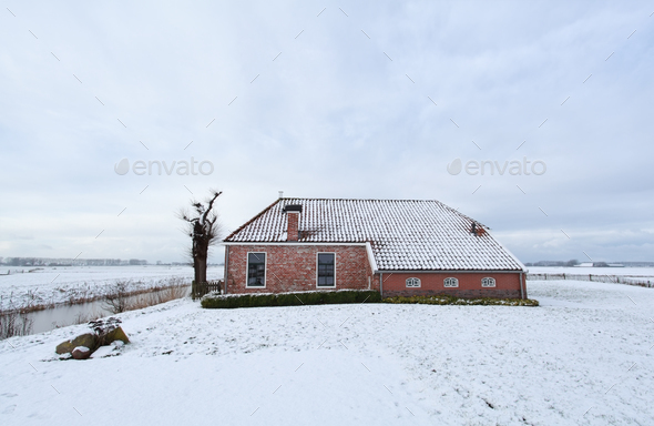 farmhouse on meadow covered with snow - Stock Photo - Images