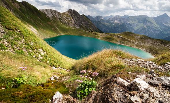 sunshine over turquoise alpine lake - Stock Photo - Images