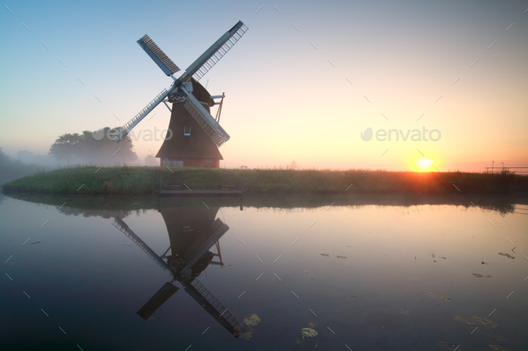 charming windmill by lake at sunrise - Stock Photo - Images