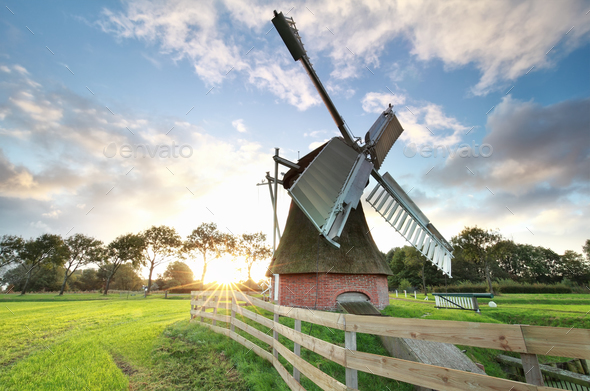 sunrise behind Dutch windmill - Stock Photo - Images