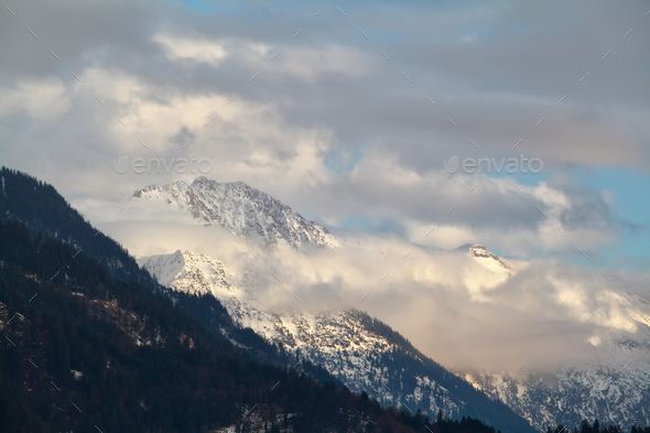 snowy mountain peaks in clouds - Stock Photo - Images