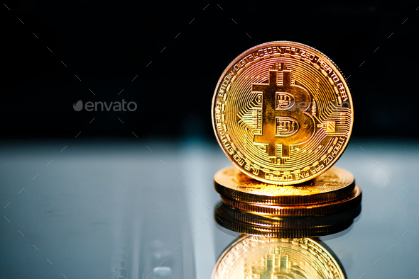 Bitcoins on reflective surface - Stock Photo - Images