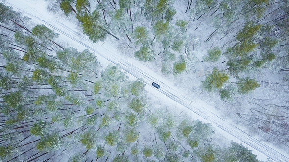 Aerial view on car driving through winter forest road. Scenic wi - Stock Photo - Images