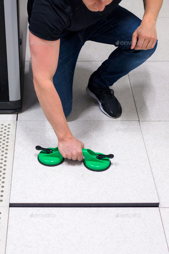 Computer Engineer Pulling Floor Tile Using Suction Cups In Datac - Stock Photo - Images