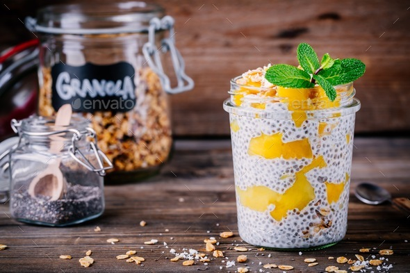 healthy vegan breakfast, chia pudding with mango and granola in the jar on wooden background - Stock Photo - Images