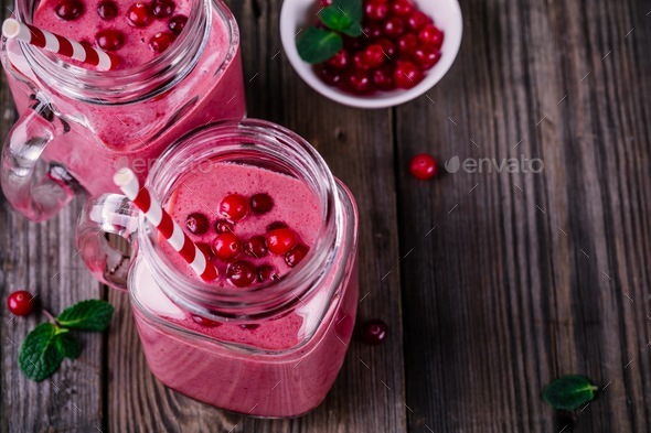 pink smoothie with wild cranberries in mason jar with mint and straw on wooden background - Stock Photo - Images