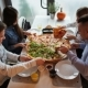 Young Friends Eating a Pizza at the Pizzeria, Talking and Laughing - VideoHive Item for Sale