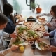 Young Friends Are Eating a Huge Pizza at the Restaurant, Talking and Laughing - VideoHive Item for Sale