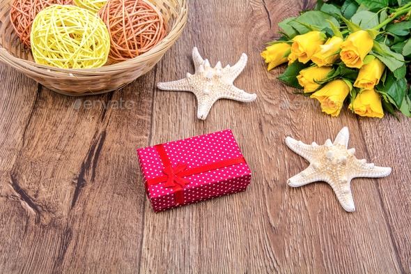 Starfishes, gift and roses on a wooden table - Stock Photo - Images