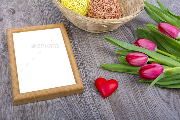 Picture frame, heart and tulips on a wooden desk - Stock Photo - Images