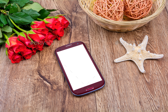 Mobile phone, starfish and roses on a wooden table - Stock Photo - Images