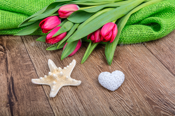 Starfish, heart and tulips on a wooden table - Stock Photo - Images