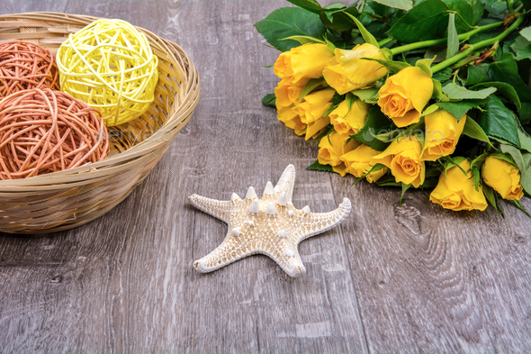 Starfish, gift and roses on a wooden table - Stock Photo - Images