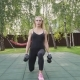 Muscular Fitness Woman Doing Walking Lunges with Dumbbells in Park - VideoHive Item for Sale
