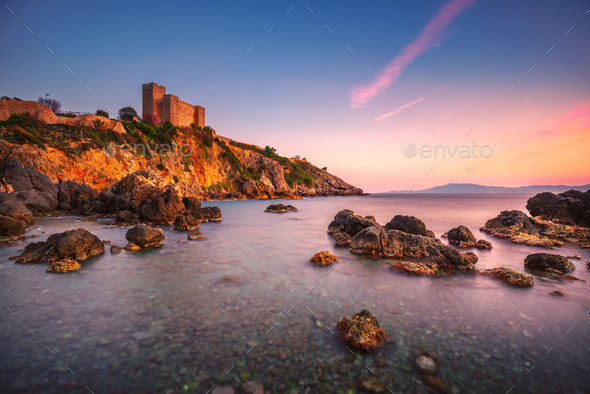 Talamone rock beach and medieval fortress at sunset. Maremma Arg - Stock Photo - Images