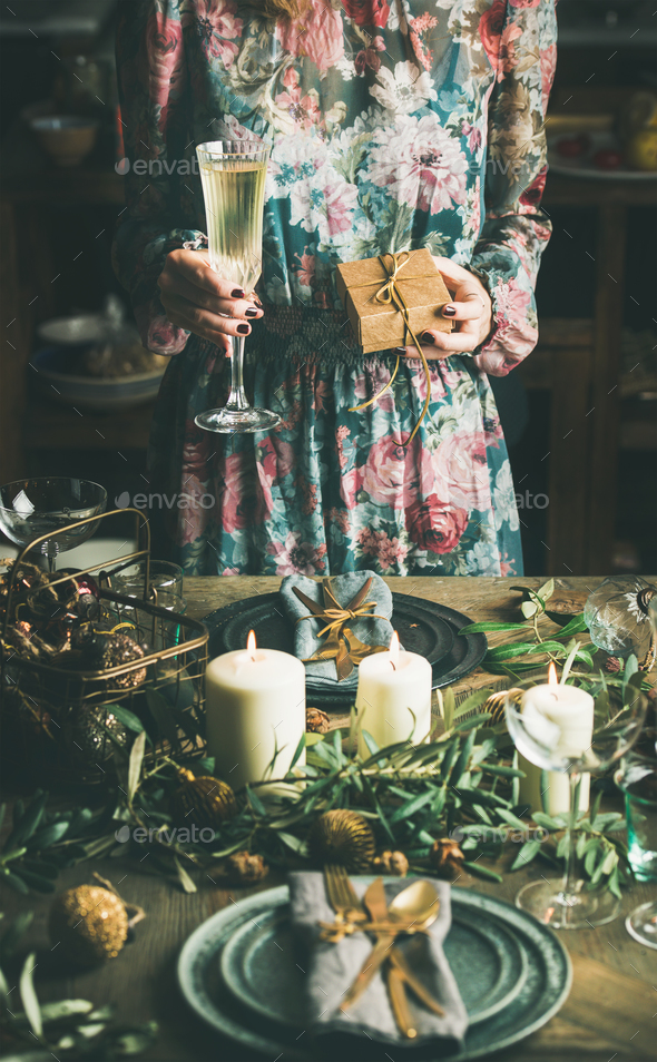 Woman holding glass of champaigne and gift box, Christmas eve - Stock Photo - Images