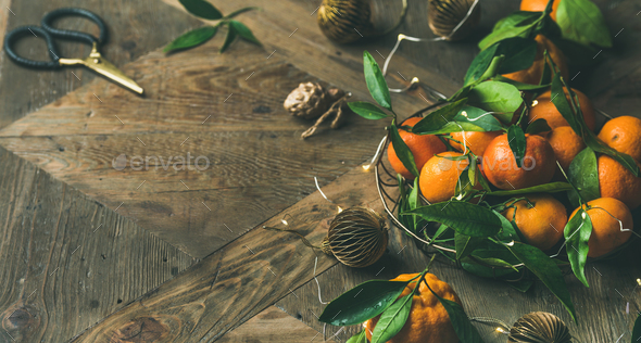 Fresh tangerines with leaves and decoration toys over wooden table - Stock Photo - Images