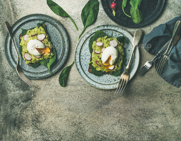 Healthy vegetarian breakfast flat-lay. Avocado and poached egg toasts - Stock Photo - Images