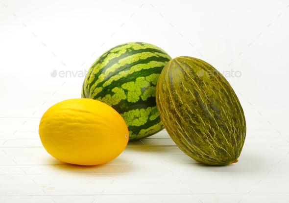 various types of melon on white wooden background - Stock Photo - Images
