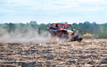 Red buggy rushes through the field in the dust - PhotoDune Item for Sale