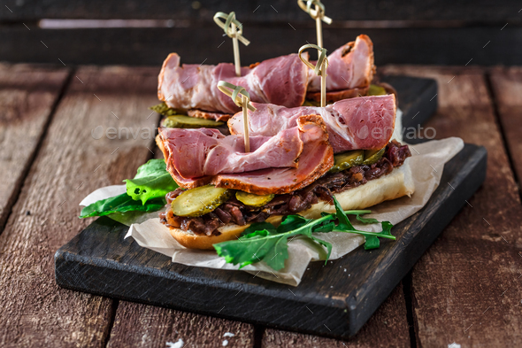 Delicius sandwiches with smoked pork, cucumbers and onion on a black wooden board - Stock Photo - Images