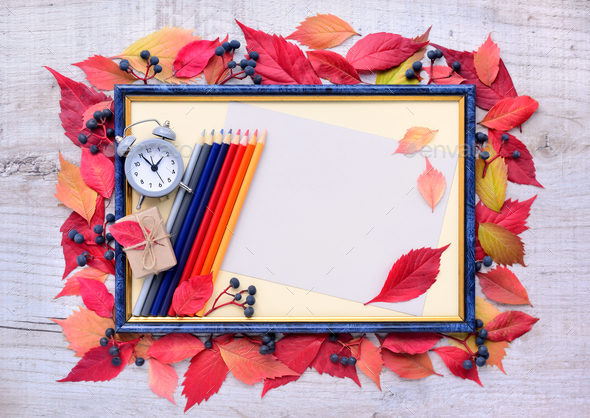 Autumn leaves composition with picture frame, alarm clock, penci - Stock Photo - Images