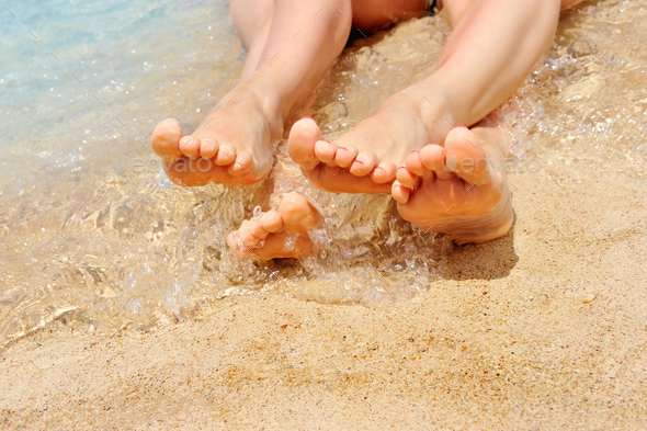 A wet female feet on the beach and sand - Stock Photo - Images