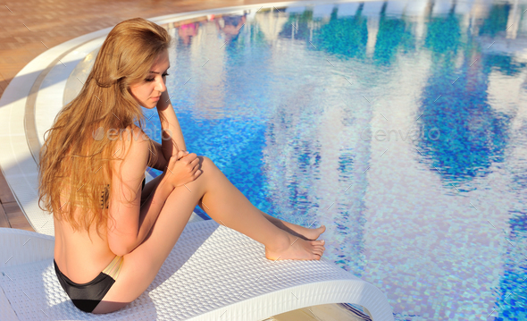 Sexy young woman on a lounger near swimming pool with blue water - Stock Photo - Images
