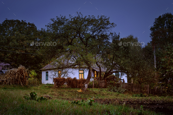 Old hut in village autumn evening scene - Stock Photo - Images