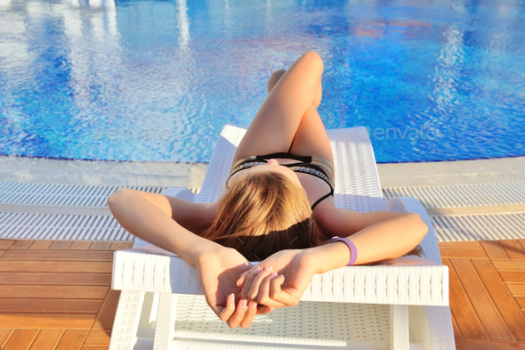 Sexy young woman lying on a lounger near swimming pool with blue - Stock Photo - Images